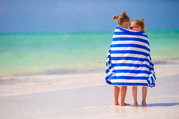 Girls wrapped in towel arter swimming at tropical beach