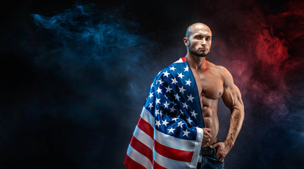 Handsome power athletic man bodybuilder with US flag. Fitness muscular body on dark smoke background. Perfect male. Awesome bodybuilder, posing.