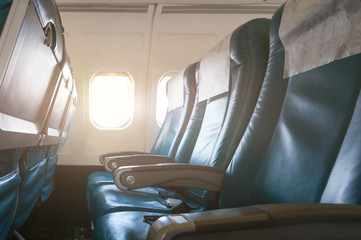 Interior of airplane with empty seats and sunlight at the window. Travel concept