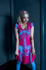 Beautiful blonde girl with two pigtails, with creative doll make-up: pink glossy lips, wearing pink skeleton dress. for the Halloween party.