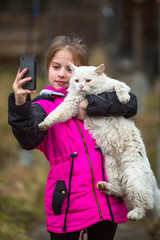 Little girl standing on the street taking a selfie with a stray cat.