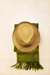 Straw hat and scarf in hipster style on wooden background.