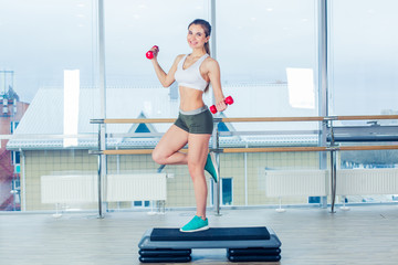 Happy young woman is doing exercises with dumbbells on step board.