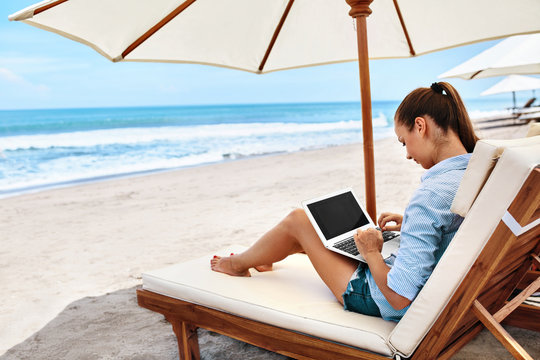 Work At Beach. Successful Business Woman Working Online In Internet Using Laptop Computer Outdoors. Girl Typing On Keyboard While Relaxing By Sea In Summer. Communication Technology Concept