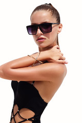 Woman in black sunglasses and swimsuit wearing golden bracelet with hair up poses on isolated white background. Fashion tan model. Beautiful awesome cool girl. Phuket island, Thailand.