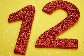 Number twelve red color over a yellow background. Anniversary