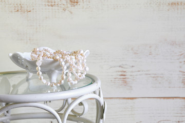 white pearls necklace on vintage table. selective focus