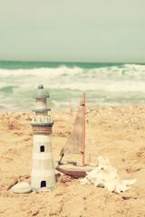 lighthouse, sailboat on sea sand and ocean horizon.