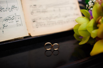Wedding rings on piano and musical notes
