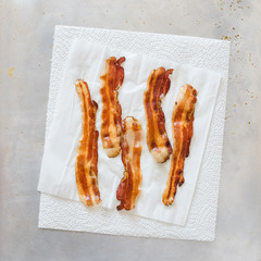 Fried crisp streaky bacon lying on the white paper towel to drain the fat