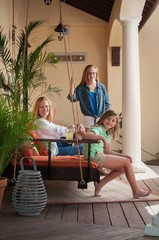Side view of mother with daughters, sitting on porch swing looking at camera smiling