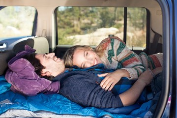 Young couple lying down in recreational vehicle, smiling