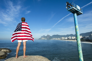 Athlete draped in American flag standing at Arpoador with a view of Rio de Janeiro skyline with Ipanema Beach and Two Brothers Mountain