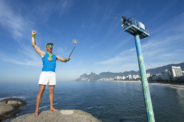 Athlete with gold medal posing for a celebratory selfie on Arpoador with Ipanema in the background.