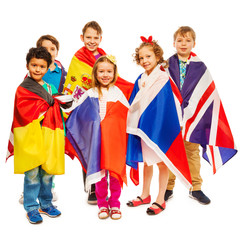 Six kids wrapped in flags of European nations