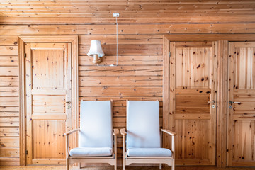 Pinewood interior wall with armchairs and doors in cabin cottage.