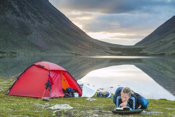 Mature woman camping at lake