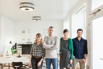 Colleagues in office side by side looking at camera smiling