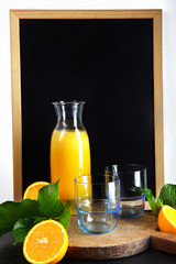 chalk board, and fresh orange juice in glasses and carafe