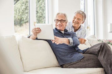Two men at home, looking at digital tablet