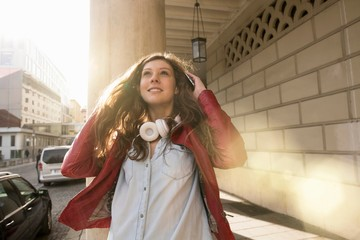 Woman wearing headphones around neck enjoying sun outdoors