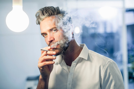 Man smoking a cigarette looking at camera