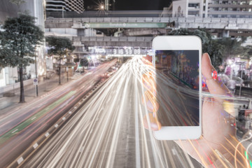 hand holding smartphone with traffic jam in the city background.