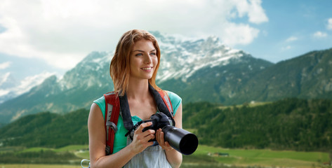 woman with backpack and camera over mountains