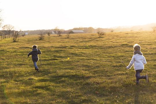 Boys running through meadow