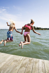 Boy and girl jumping into water