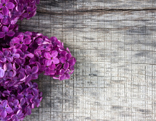 bouquet of purple lilac flowers on old gray wooden background. with space for posting information