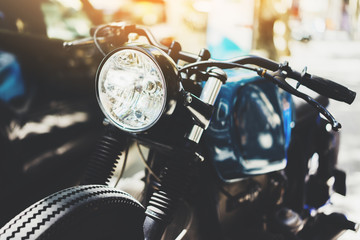 Close-up of vintage custom motorcycle outdoors, hipster cafe-racer at the parking outside, flare light, visual effects