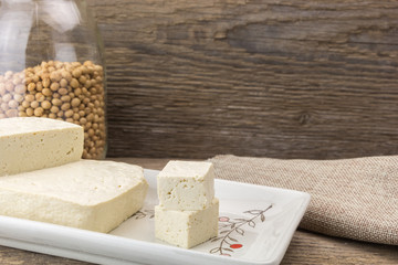 Tofu and soybeans in vase, on wooden background.