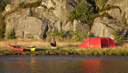 Female hiker camping near river