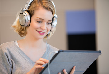 Young woman listening music on pad