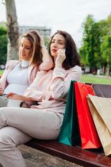 Two women using mobile phone after shopping