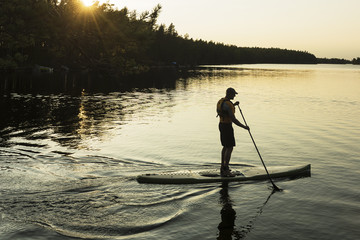 Man on paddle board at sunset