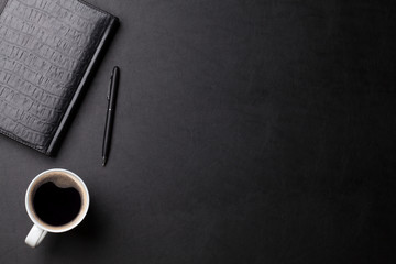 Office desk with coffee, notepad and pen