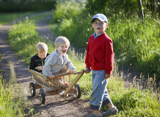 Children playing with wooden cart