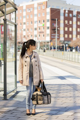 Woman on tram stop with dog in bag