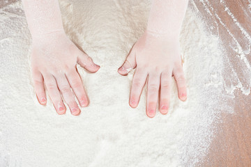 Children's palms in flour on the kitchen table