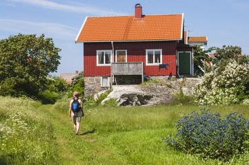 Woman walking near wooden house