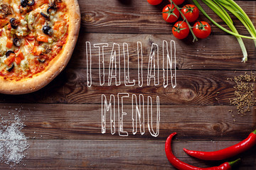 Italian pizza with tomatoes on a wooden table, top view, close-up