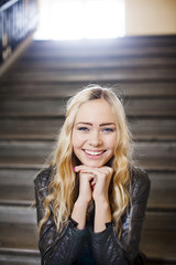 Portrait of smiling woman sitting on stairs