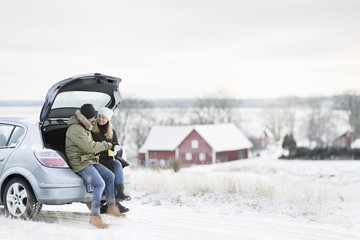 Smiling couple sitting in open boot
