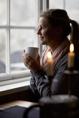 Woman having coffee and looking through window