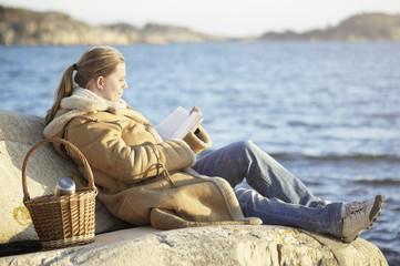 Woman reading book at sea
