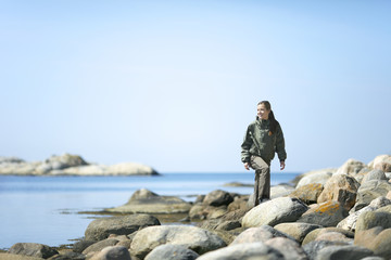 Woman walking on rocky coast