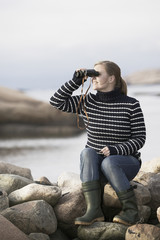 Woman looking at sea through binoculars