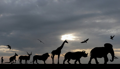 Silhouettes of animals on sea sunset with grey cloudy sky background